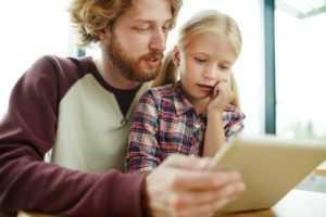 Forældre hjælper barn på digitale medier
